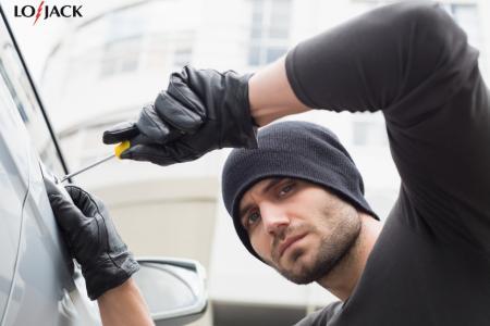 złodziej samochodu przy aucie